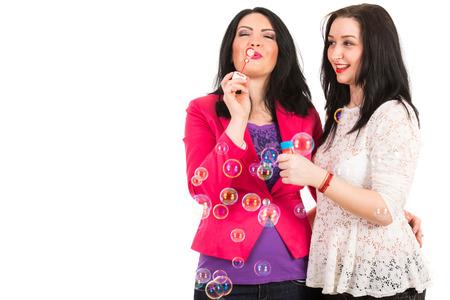 blow out: Amici felici le donne havin divertimento insieme e soffiare bolle di sapone isolato su bianco