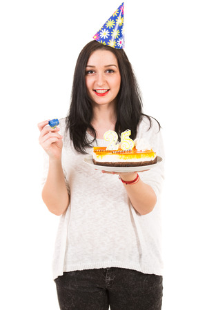 Cheerful woman with party hat holding birthday cake isolated on white  photo