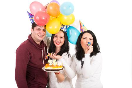 blow out: Felici tre amici in donna di compleanno con torta e palloncini soffiare corno partito isolato su bianco Archivio Fotografico