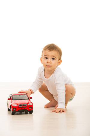 boys toys: Lovely baby boy playing with a big car toy on floor