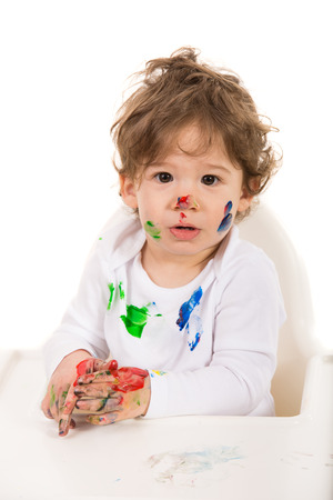 Toddler boy with messy face and hands sitting in a high chiar  photo