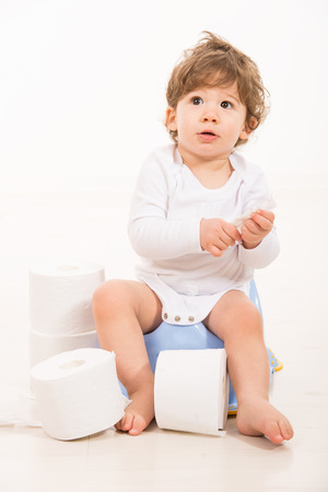 Amazed toddler boy on potty looking up and thinking photo