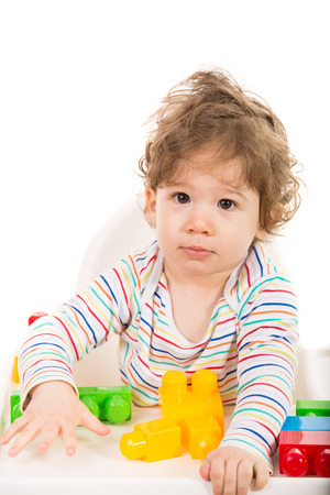 high chair: Toddler boy sitting in a high chair and playing with building  blocks Stock Photo