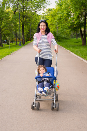 Happy mom pushing pram with toddler boy in park photo