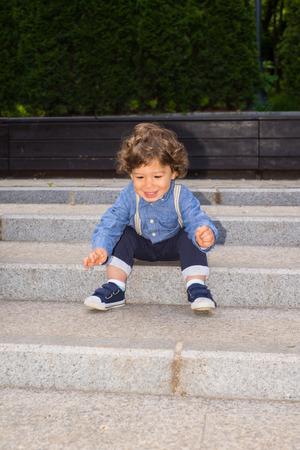 bajando escaleras: Niño feliz en las escaleras tratando de levantarse