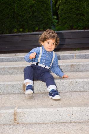 bajando escaleras: Muchacho del niño tratando de descender las escaleras en la parte inferior Foto de archivo