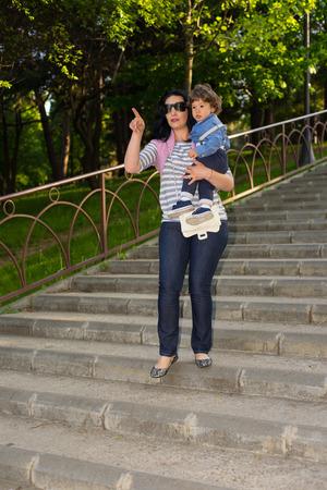 bajando escaleras: Madre con el niño camina hacia las escaleras y señalando algo en un parque