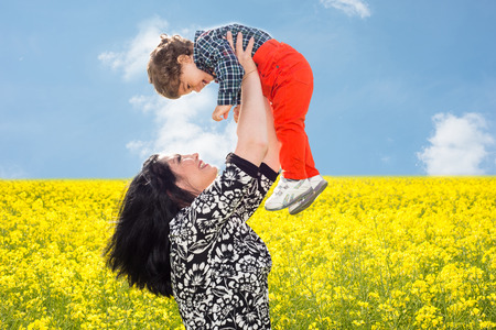 togther: Mother raise up her todller son in canola field and having fun togther