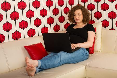 trabajando en casa: Mujer embarazada que trabaja en casa y sentado en el sof�