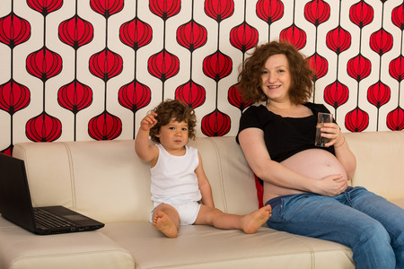 Cheerful pregnant mom and toddler boy sitting on couch and having conversation photo