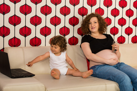 Pregnant mother sittingon couch and her toddler son pointing something to laptop photo