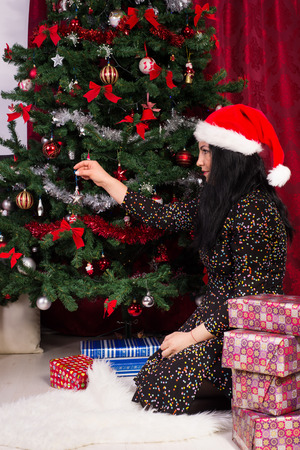 decorates: Woman sitting down  and decorates Christmas tree