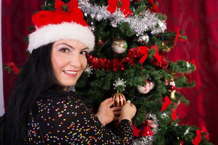 decorates: Happy woman with santa hat decorates Christmas tree