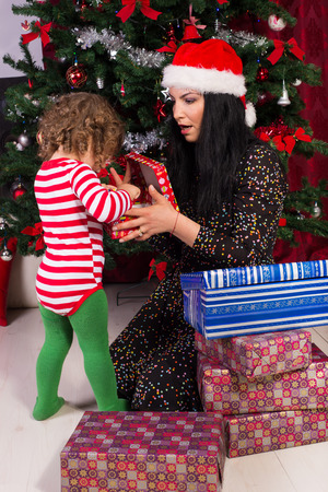 Amazed mother and toddler boy opening Christmas gifts under tree photo