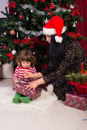 baby open present: Mother helping toddler boy to open his Christmas gift