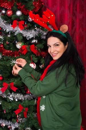 decorates: Christmas woman decorates her tree with snowflakes and wearing reindeer ears Stock Photo