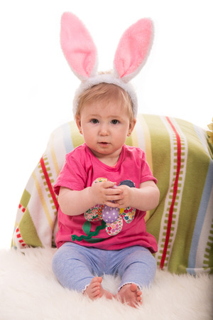lilla: Cheerful baby girl with bunny ears holding lilla Easter egg and sitting on fluffy blanket Stock Photo