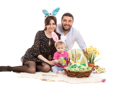 Happy Easter family sitting on fluffy blanket with their little daughter photo