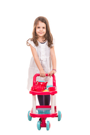serve one person: Little girl playing waiter and  pushing trolley pram with cups and kettle isolated on white background