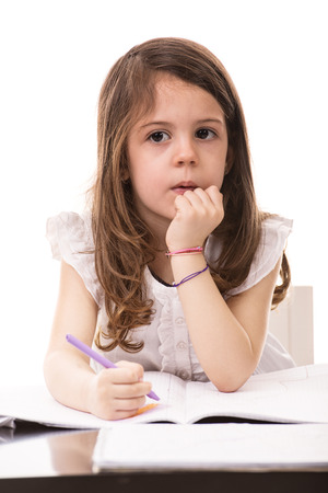 inddor: Thinking little girl drawing in kindergarten isolated on white background