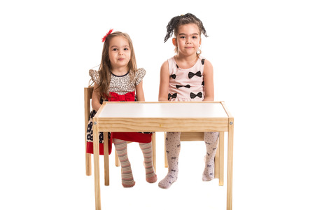 wry: Two girls sitting on chairs at table and make wry mouths together isolated on white background