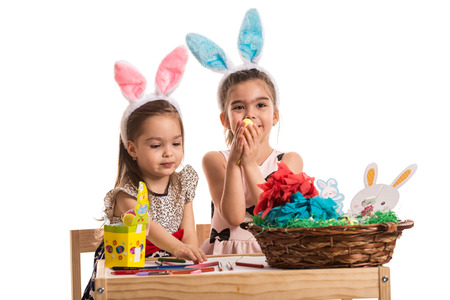 Two little girls in kindergarten sitting at table and painting and decorating Easter eggs photo