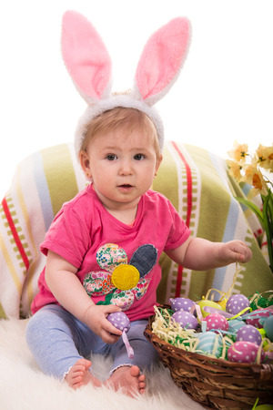 Beauty baby with pink bunny ears holding easter eggs  and sitting on fluffy blanket photo