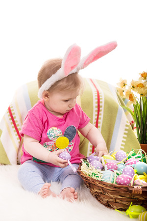lilla: Baby girl with bunny ears choose easter eggs from basket Stock Photo