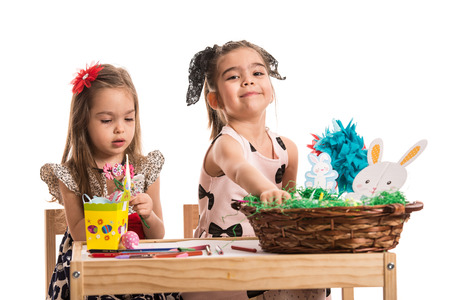 Two girls sitting on chairs at table and painting Easter eggs photo