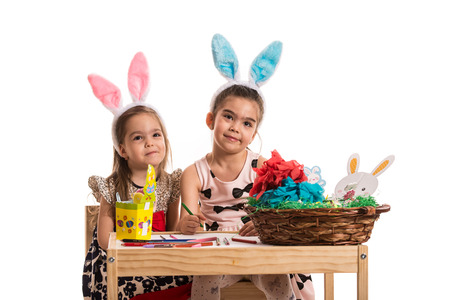 creative egg painting: Two girls with bunny ears painting Easter eggs and make a wry faces  and sitting together at table