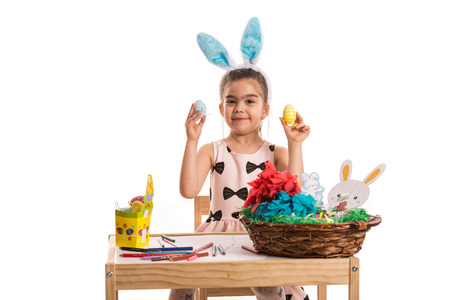 Happy girl with bunny ears showing painting Easter eggs against white background photo