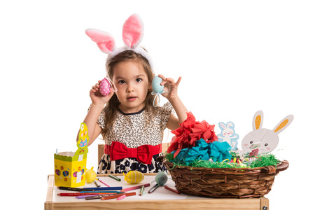 Little girl with pink fluffy bunny ears showing colorful Easter eggs photo