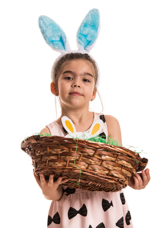 Girl with blue bunny ears holding basket with eggs isolated on white background photo