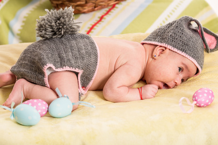 Newborn baby girl in crochet bunny costume with Easter eggs photo