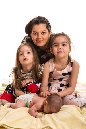 three girls: Mother posing with her three girls daughters against white background Stock Photo