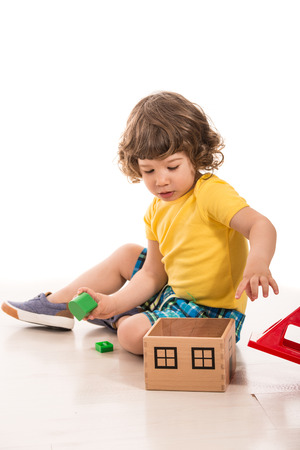 adding: Toddler boy playing with wood house toy adding cubes