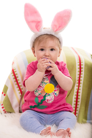 Expressive baby girl with fluffy bunny ears  eating a Easter toy egg photo