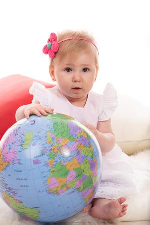inflate: Amazed baby girl holding inflate world globe Stock Photo