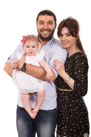 portrait studio shot: Happy mother,father and baby girl smiling together isolated on white background