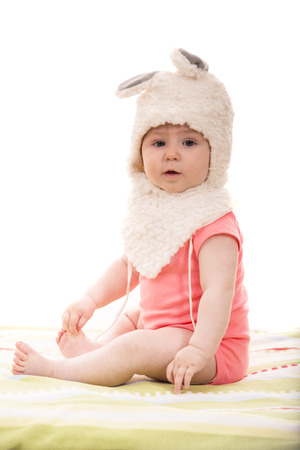 girl sitting down: Baby girl sitting down and wearing fluffy bunny hat with ears