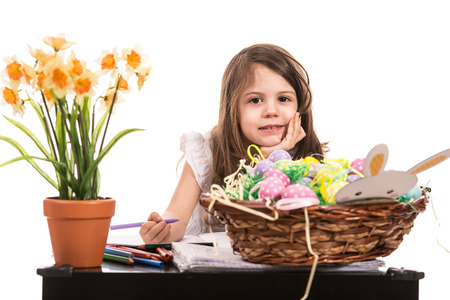 Beauty little girl at kindergarten painting Easter eggs photo