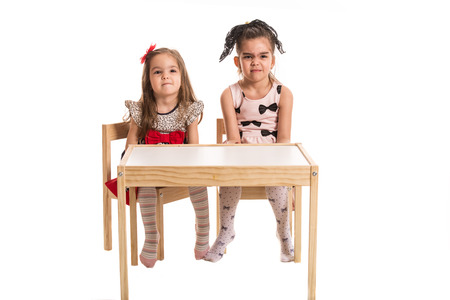 wry: Full length of two girls sitting at table and make wry faces isolated on white  background Stock Photo