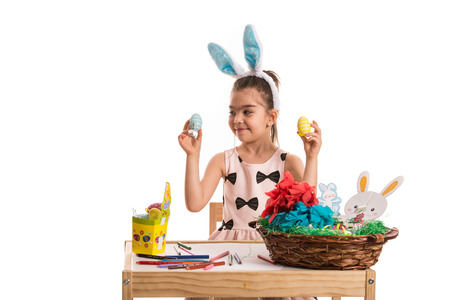 Little girl with bunny ears sitting at table and choose Easter egg photo