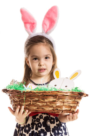 Preschool girl with bunny ears holding basket with easter eggs isolated on white background photo
