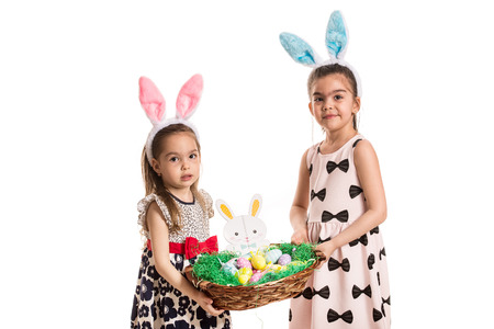 Two sisters with fluffy bunny ears holding basket with easter eggs isolated on white background photo