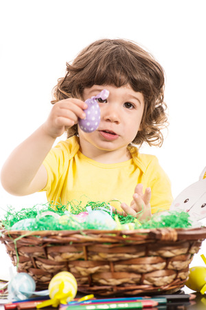 lilla: Toddler boy showing lilla easter egg from basket isolated on white background