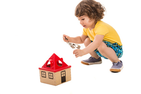 toddler boy: Little boy holding keys  to open  wooden house toy isolated on white background
