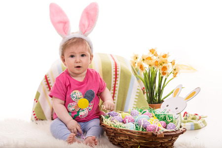 Cute baby girl with fluffy bunny ears and basket with Easter eggs photo