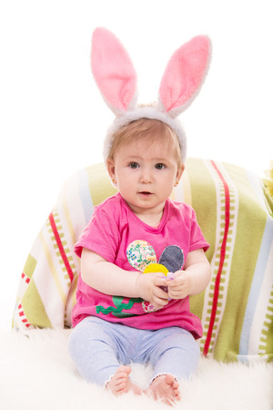 lilla: Expressive baby girl with fluffy bunny ears holding Easter egg