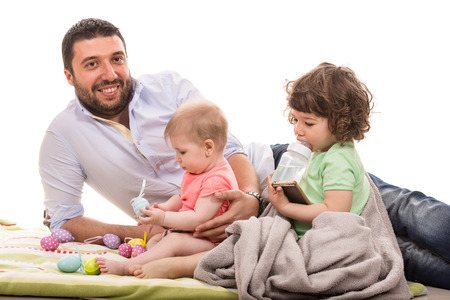 Happy father laying together with his baby daughter and toddler boy photo